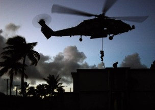 """060620-N-6074Y-119 Guam (June 20, 2006) - Navy Special Warfare (NSW) Sailors fast rope onto a rooftop from an HH-60H helicopter assigned to the """"Golden Falcons"""" of Helicopter Anti-Submarine Squadron Two (HS-2), during simulated Strike Warfare missions over the island of Guam. HS-2, part of Carrier Air Wing Two (CVW-2), embarked aboard the Nimitz-class aircraft carrier USS Abraham Lincoln (CVN 72) during Exercise Valiant Shield 2006. Valiant Shield focuses on integrated joint training among U.S. military forces, enabling real-world proficiency in sustaining joint forces and in detecting, locating, tracking and engaging units at sea, in the air, on land and cyberspace in response to a range of mission areas. U.S. Navy photo by Photographer's Mate 3rd Class M. Jeremie Yoder (RELEASED)"""