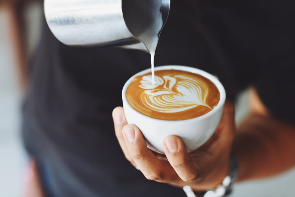 man pouring cappuccino