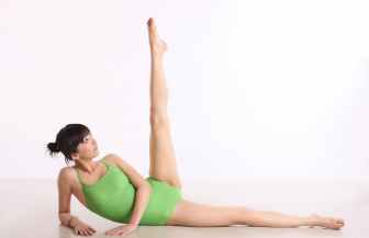 girl laying on her side with one leg up in the air with a green leotard