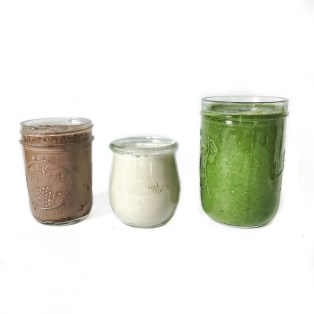 brown smoothie, white smoothie and green smoothie in glass jars