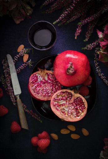 pomegranate cut open with knife next to it
