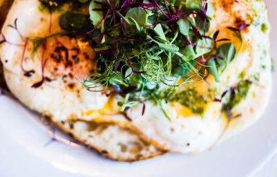 fried eggs with microgreens on top, breakfast food