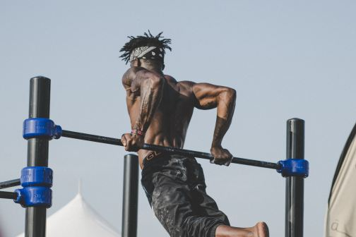 shirtless man tricep dips on bar