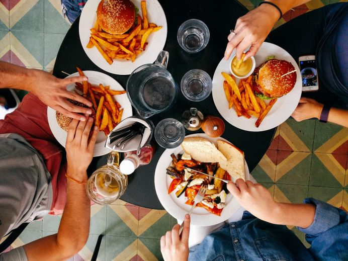 friends gather and eating burgers with hands shown