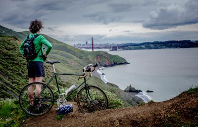 bicycle and man in the dirt looking at bridge