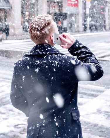 man talking on a cell phone in the snow