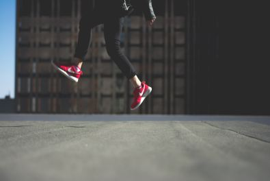 person jumping with red nikes