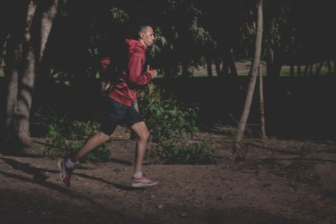 man running outside in shorts and a red jacket