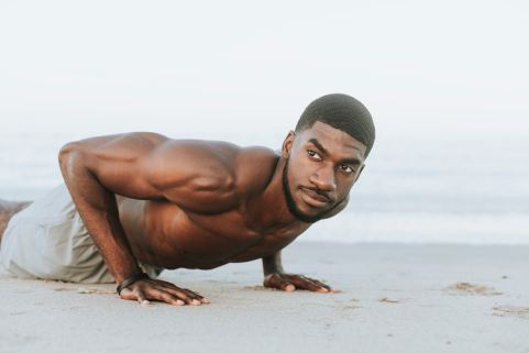 man performing pushups in the sand