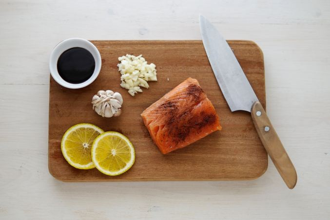 salmon on a cutting board with lemon and garlic
