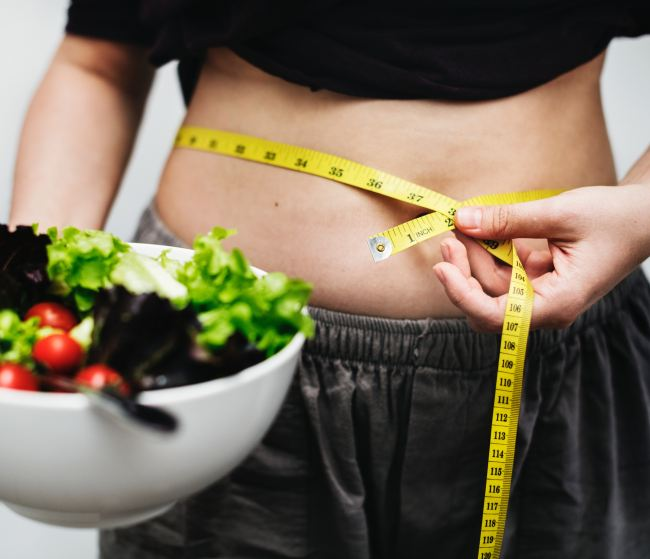 person with measuring tape around waist and a salad