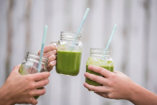 three green smoothies in mason jars with straws