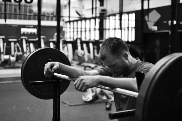 man resting on a barbell