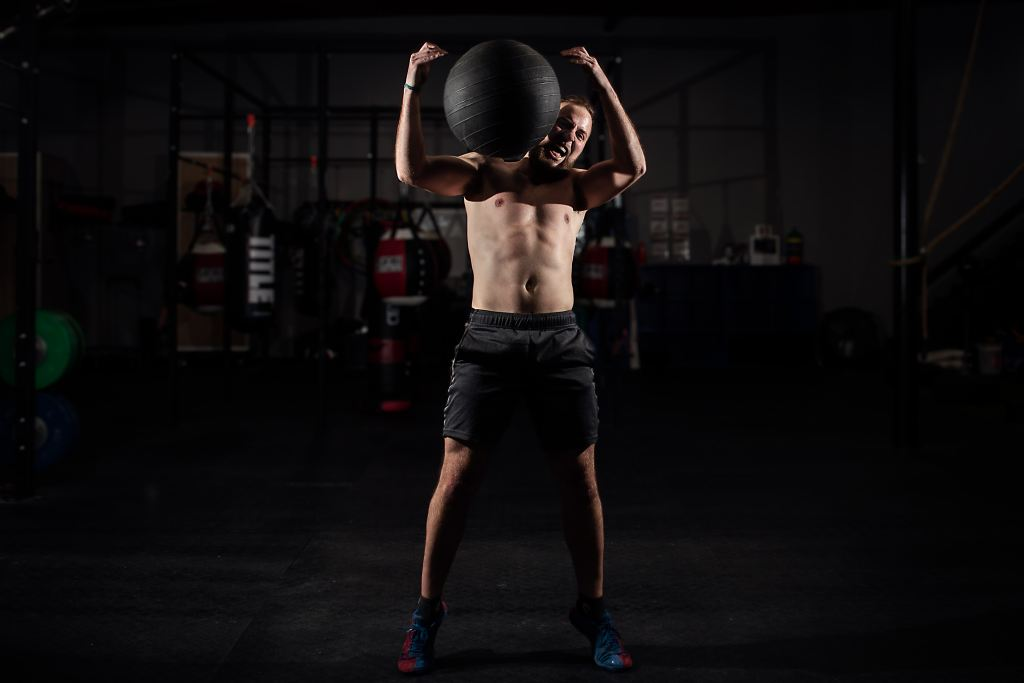 man with a weighted ball doing a football player exercise