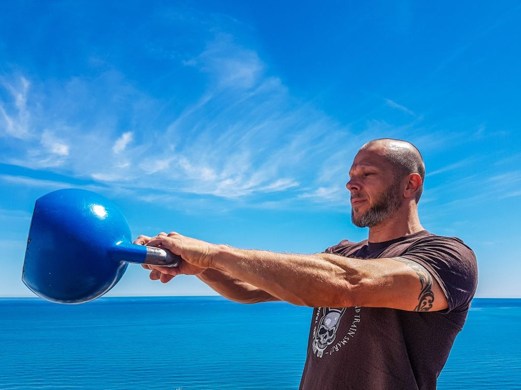 Man doing Kettlebell swings outside