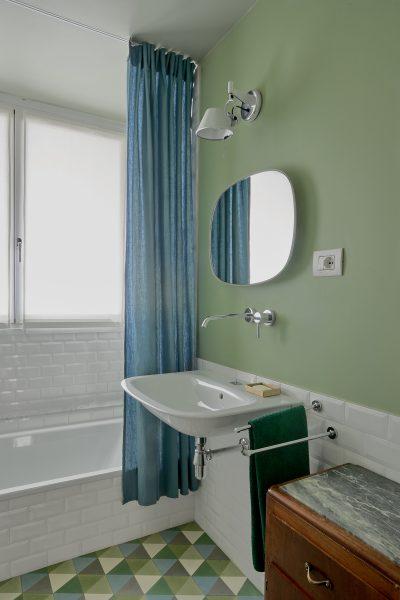 Bagno con pareti blu e cementine artigianli a pavimento