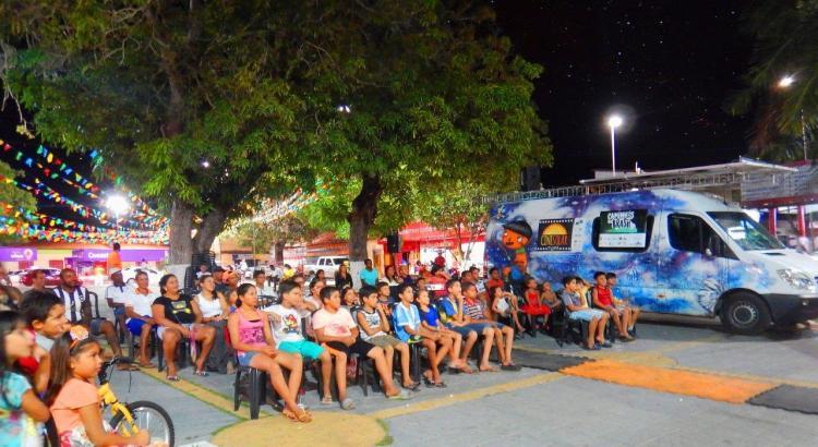 Sessão de cinema acontece em uma praça, cheia de crianças