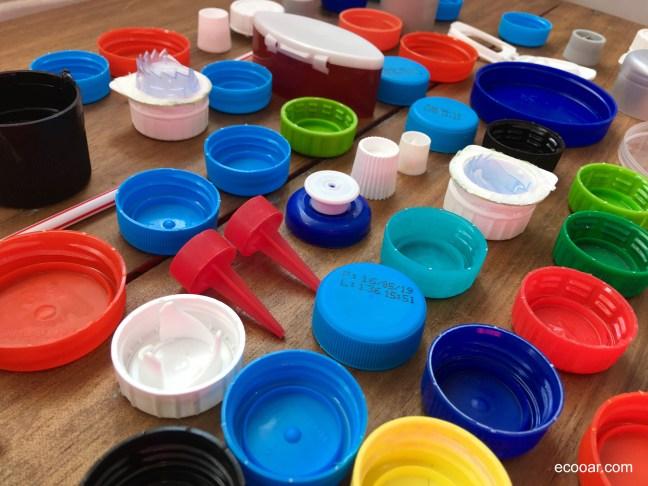 Foto mostra tampas e produtos plásticos sobre madeira