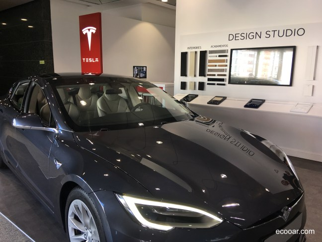Foto mostra uma loja com modelo de carro elétrico da Tesla