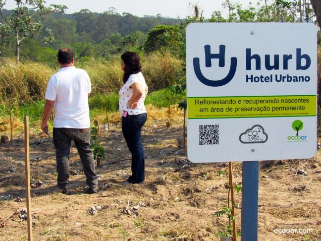 Foto mostra área de reflorestamento Hurb com placa e auditoria no dia da árvore