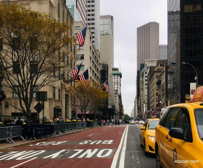 Foto mostra rua de Nova York com táxis, árvores e prédios.