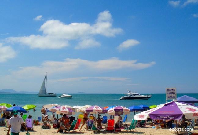 Foto mostra Praia de Jurerê Internacional com iates ao fundo