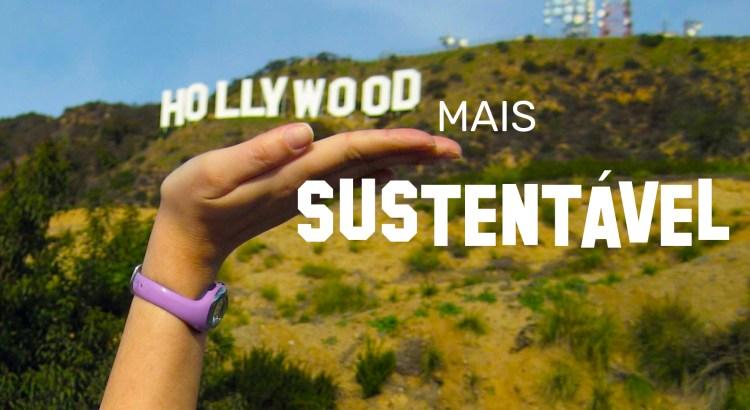 Foto mostra o letreiro Hollywood sobre um morro e uma mão sustentando o logo