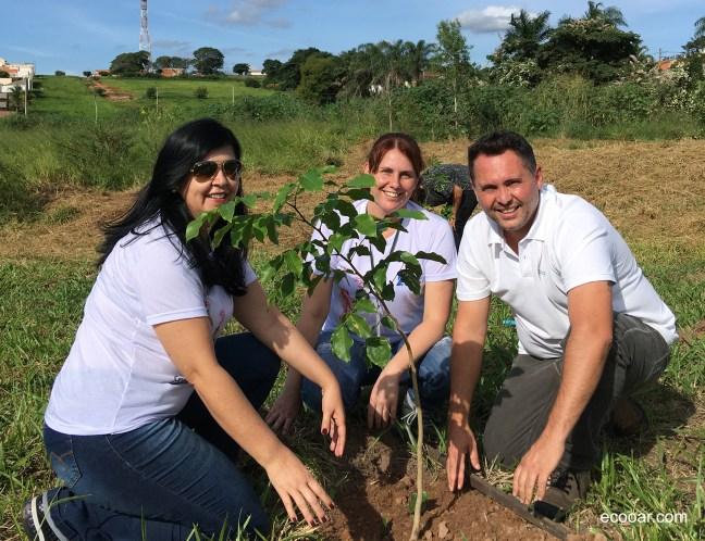 Foto contém três pessoas próximas a uma muda de árvore, que fazem parte do programa Município VerdeAzul