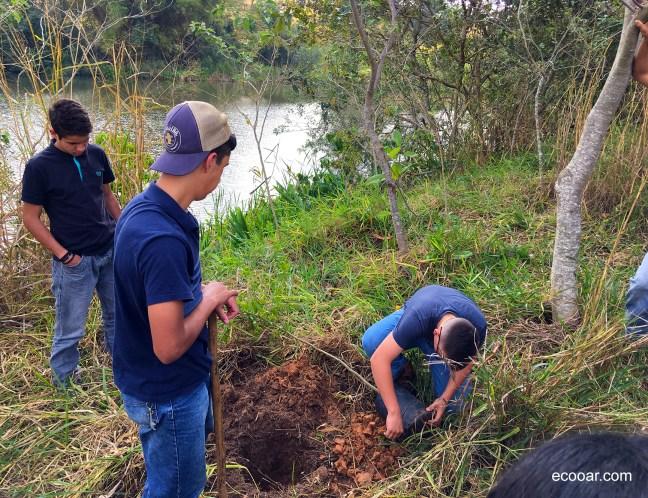 Foto contém três adolescentes plantando uma árvore para o programa Município VerdeAzul
