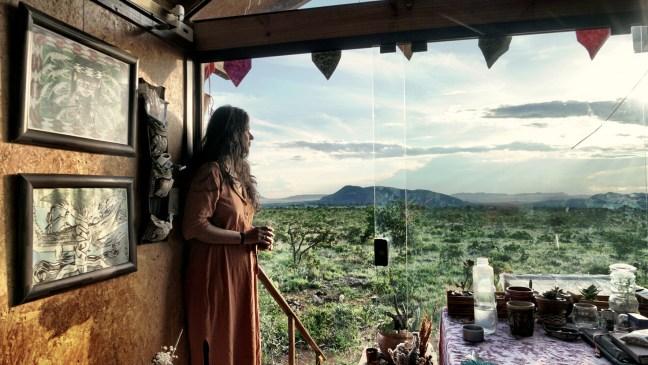 Foto mostra mulher olhando para horizonte de uma sacada