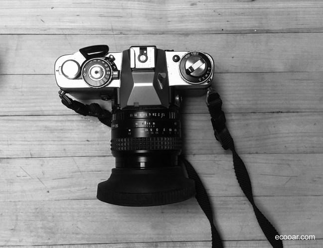 Foto mostra máquina fotográfica Minolta em cima de uma mesa de madeira