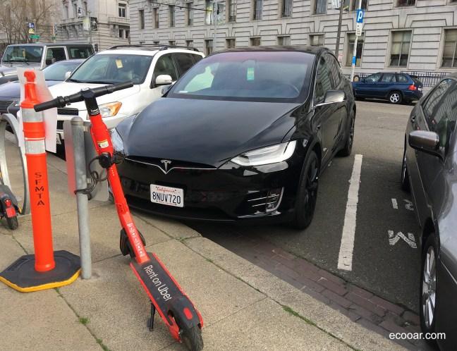Foto mostra carro elétrico Tesla e um patinete elétrico em rua de San Francisco mostrando boas práticas