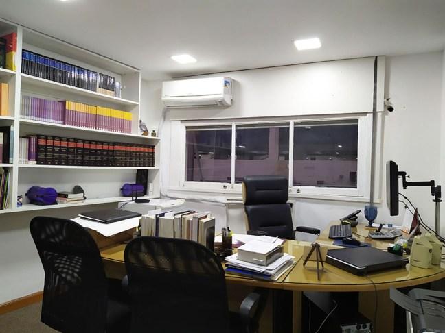 Foto mostra sala de escritório com estante com livros, mesa e três cadeiras
