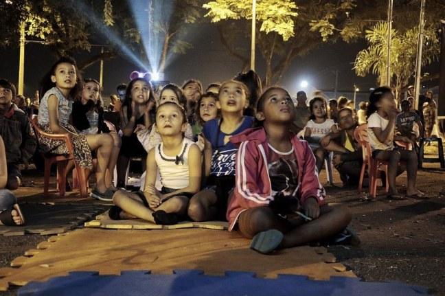 Foto mostra crianças olhando uma sessão de cinema