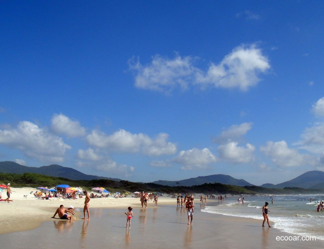 Foto mostra uma praia de água salgada e pessoas caminhando pela orla, com morros ao fundo