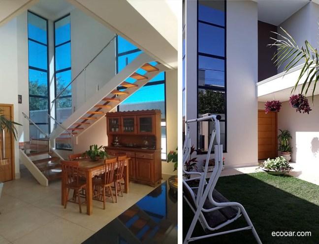 Foto mostra parte interna de casa baseada em arquitetura sustentável com escadas e grandes janelas