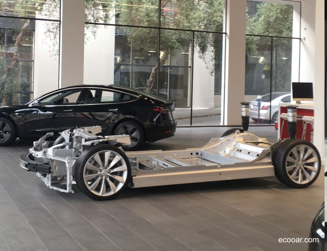 Foto mostra chassi de um carro Tesla dentro de uma loja da empresa, com outro carro ao fundo, em frente a uma grande janela
