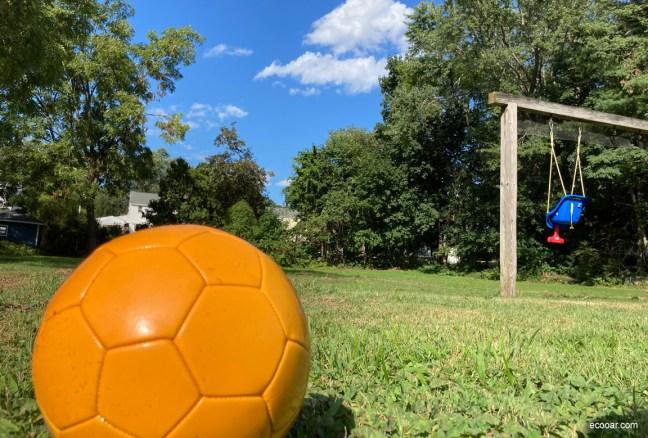 Foto mostra bola em primeiro plano, com um balanço e árvores ao fundo