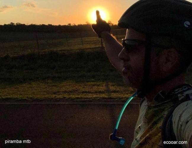 Foto mostra ciclista em uma bicicleta com um por do sol ao fundo