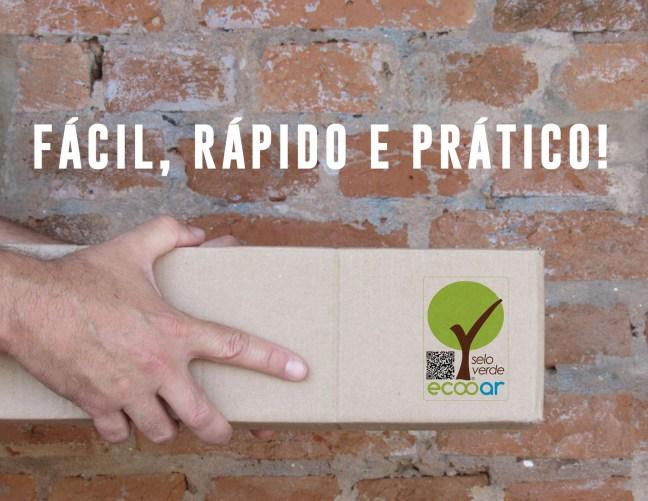 Foto mostra mão segurando uma caixa na frente de um parede com a marca Ecooar