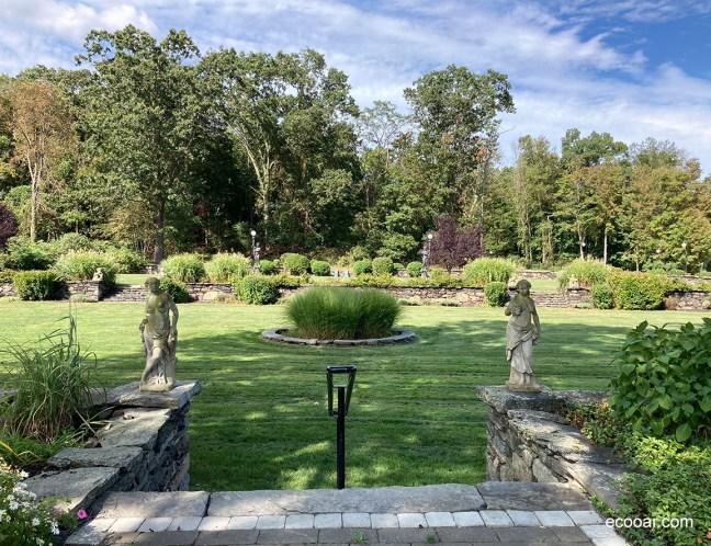 Foto mostra um jardim, adornado com duas estátuas na entrada e árvores nativas ao fundo