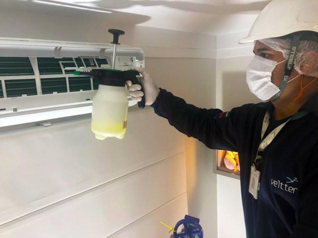 Foto mostra técnico da Veltter higienizando ar condicionado