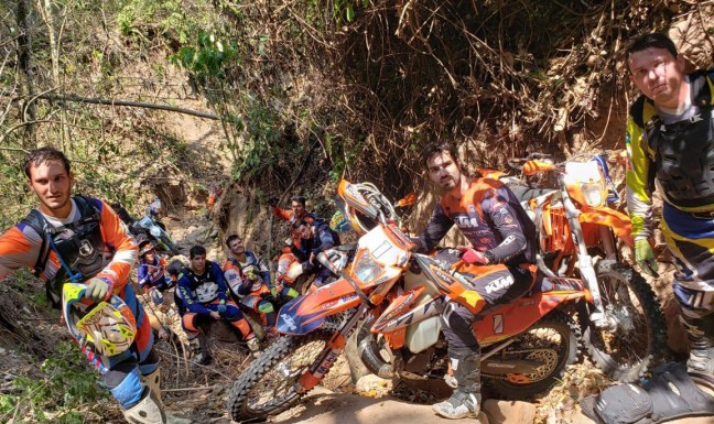 Foto mostra Rigor Rico em trilha no meio da mata junto com outros motoqueiros