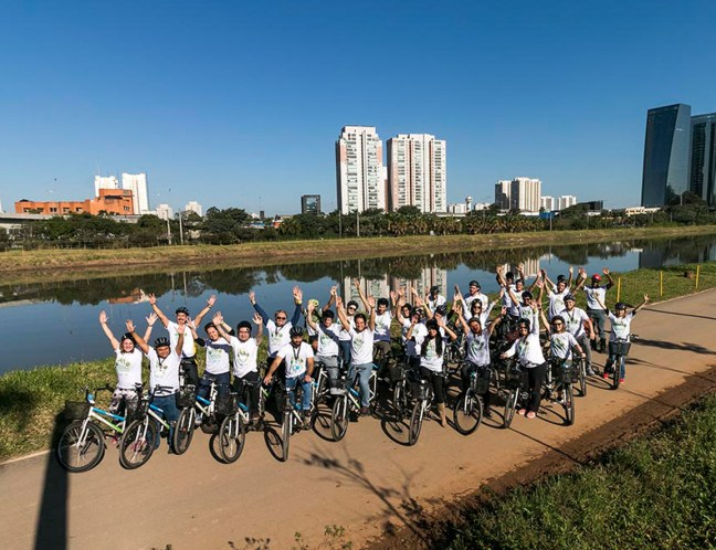 Foto mostra ciclistas em frente ao rio Pinheiros em São Paulo