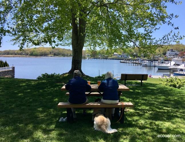Foto mostra duas pessoas sentadas em frente a um lago, com um cachorro sobre o banco, tirada em Essex, Connecticut, EUA