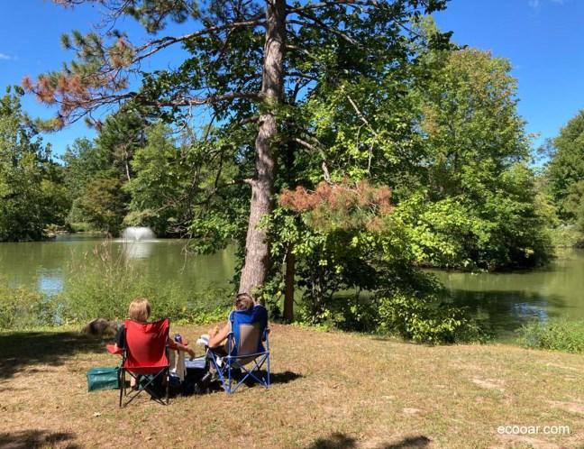 Foto mostra duas pessoas sentadas com um lago no fundo