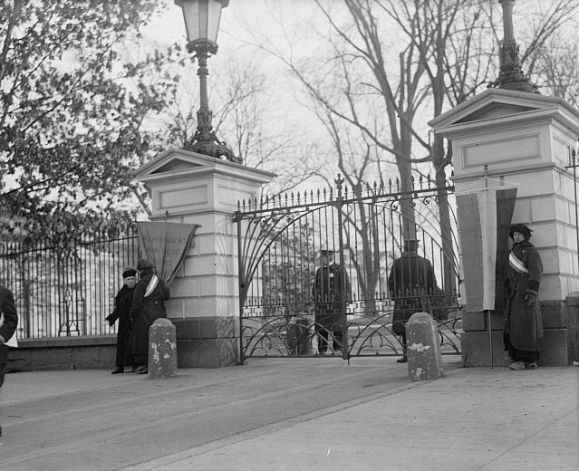 Suffragists outside the White House gates. National Photo Company via Wikimedia Commons.