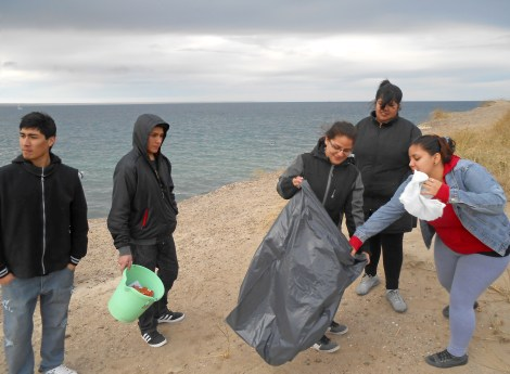 """One Day in the Life"" photograph of students from Escuela de Pesca Secondary School in Puerto Madryn, Argentina (in the Argentine Patagonia). The school is an alternative vocational high school whose entire curriculum revolves around fishing. Students are seen here collecting garbage on the beach to help protect the environment. Photograph by Soledad Gómez Saá."