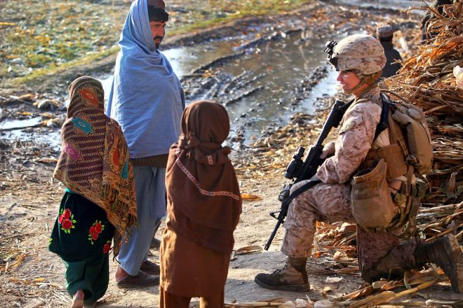 Securing more opportunities for Afghanistan's women and girls became a thread stitching through many U.S. policy decisions. Here, U.S. Marine Corps Corporal Brandy Bates stops to talk with Afghan children and their father during a foot patrol through the village of Tughay, in Helmand province. Photograph by Corporal Meredith Brown, U.S. Marine Corps, courtesy Wikimedia