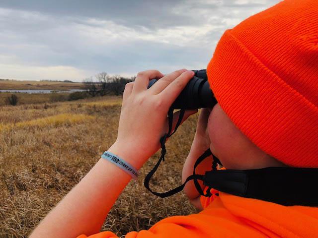 A student looks at prairie lands through binoculars